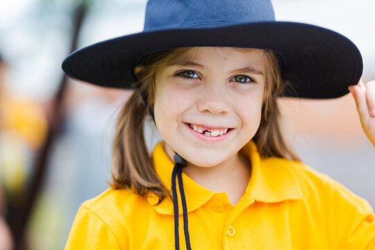 Portrait of a happy young school girl outside wearing a hat for sun protection