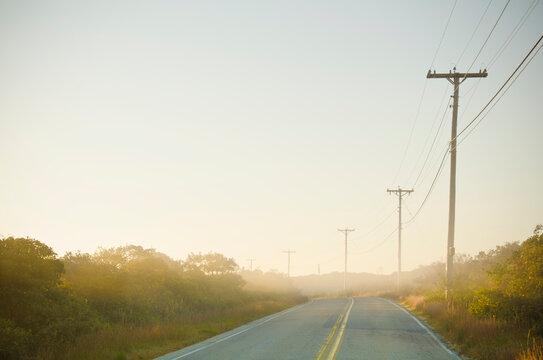 USA, Massachusetts, Cape Cod, Nantucket Island, Empty country road at sunrise