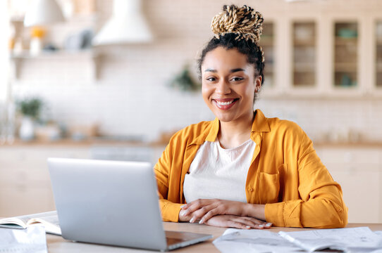 Joyful cute good looking young African American woman with dreadlocks, freelancer, manager, student, in casual wear, working remotely on laptop, sits at work desk, looks at the camera, smiles friendly