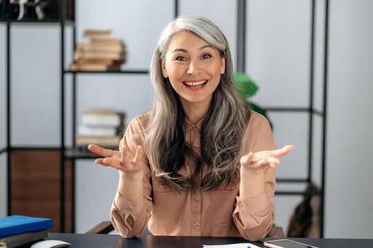 Happy attractive successful mature Asian business woman, manager, sitting at the table, talking by online conference, video call with business team or family, gesturing with hands, smiling
