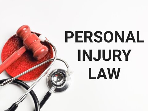 Medical and law concept. Selective focus phrase PERSONAL INJURY LAW written on white background with gavel and stethoscope.