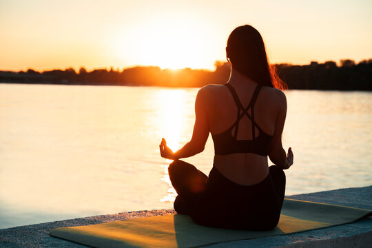 Back view of young woman meditating in sunset , by the river