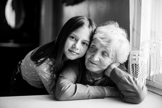 Little girl hugs her grandmother. Black and white portrait.