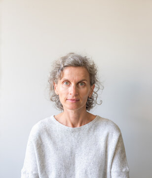 Head and shoulders view of casually dressed natural looking middle aged woman with grey hair against neutral background (selective focus)
