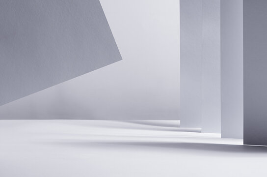 Abstract geometric white grey minimalist background with perspective of walls, stripes and flying paper in light and shadow as border, copy space.