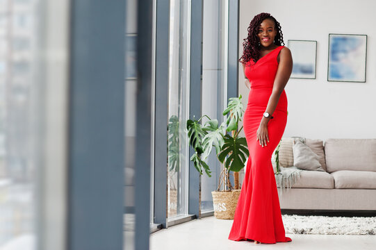 Magnificent young african woman in luxurious red dress in a luxury apartment. Beauty, fashion.