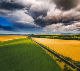 Wall Mural - Aerial top view of ominous storm clouds over fresh field.