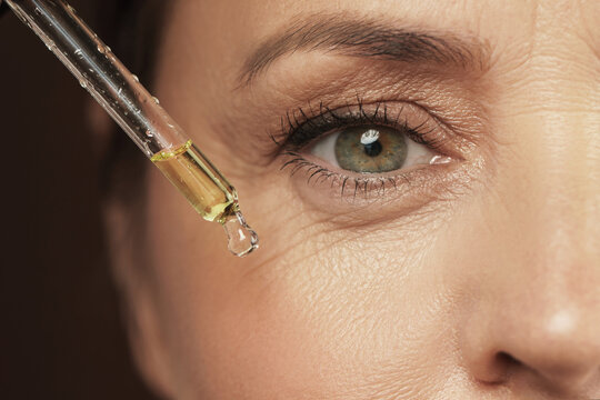 Female eye and dropper with rejuvenating serum