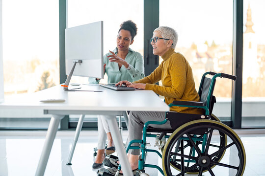 Senior business woman in wheelchair working in office