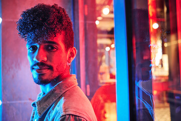 young hispanic man close to a neon light with blue and red lights