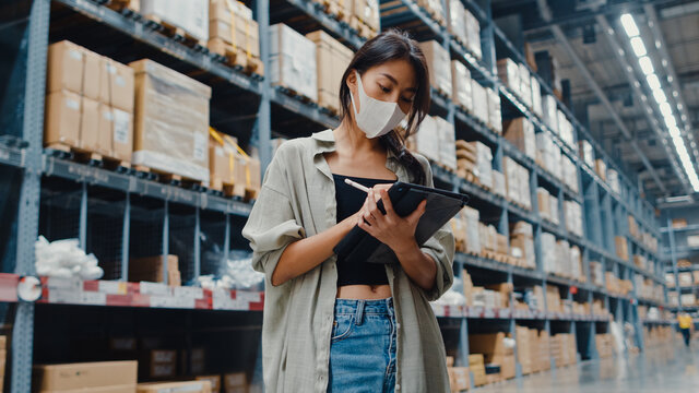 Young Asia businesswoman manager wear face mask looking for goods using digital tablet checking inventory levels stand in retail shopping center. Distribution, Logistics, Packages ready for shipment.