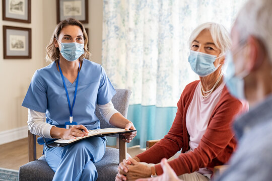 Nurse listening to senior couple during a home visit