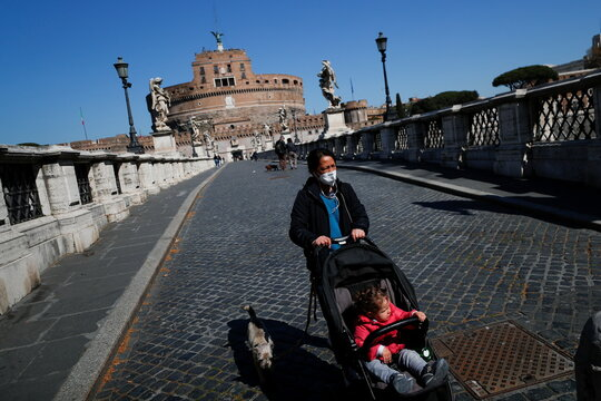 A woman wearing a face mask pushes a baby stroller on Sant'Angelo bridge as COVID-19 restrictions in the Lazio region are slightly relaxed, in Rome