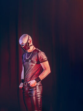 Dark creative artistic portrait of a rubber fetish, latex young man with fashion rubber outfit, harness and mask.Post Apocalyptic super villain concept.