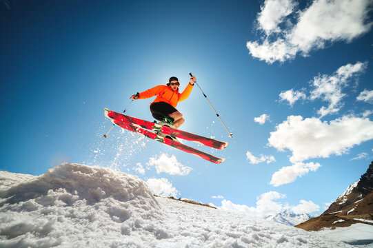 young caucasian guy jumping from a springboard on skis