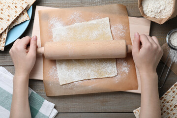 Woman rolling raw dough for traditional matzo at wooden table, top view