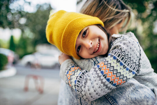 Candid portrait of a happy little girl in the yellow hat hugging her mom. Happy kid embracing her mother enjoying the time together outside. Joyful mom and daughter share love. Mother's day
