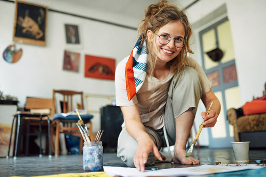 Full-length view of a pretty female artist sitting on the floor in the art studio and painting on paper. A woman painter with glasses painting with watercolors in the workshop.