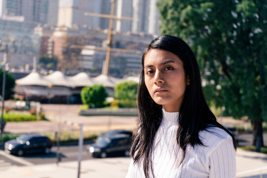 Mid-shot portrait of a serious black-haired Latina woman with the city in the background.