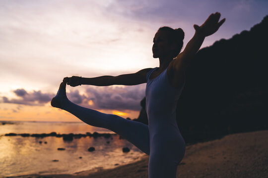 Silhouette view of young fit girl practicing yoga at seashore during sunset time on recreation, flexible female doing asanas for stretching body muscles feeling harmony and mindfulness on nature