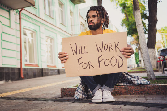 Photo portrait of hungry man holding carton table looking for job need new work will work for food