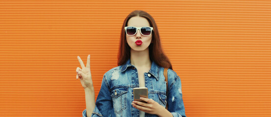 Portrait close up of young woman with smartphone wearing a denim jacket posing on an orange...