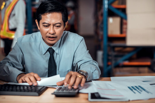 Stressed businessman worry about financial balance trouble of his company at his office in warehouse. Profit less than target while global corona virus or Covid-19 crisis, negative emotional concept