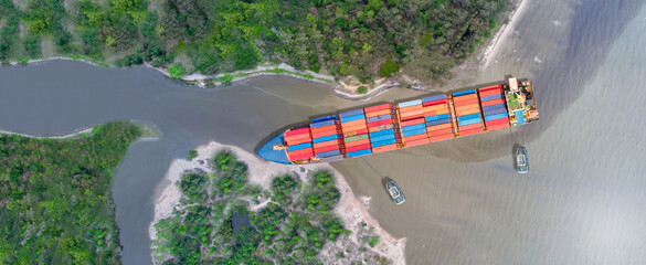 Obraz Canal blocked by huge cargo container ship; Aerial top view of accident container ship with salvage crews across the canal concept accident safety and insurance. - fototapety do salonu