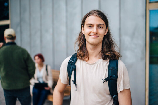 Portrait of smiling male student against gray wall in campus