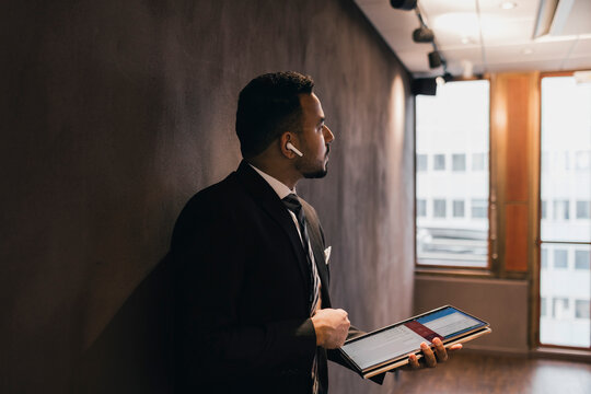 Thoughtful male professional holding digital tablet looking away while leaning against wall in board room at office