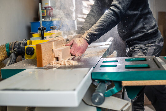 Professional carpenter cutting the wood on the  huge saw for a modern furniture, joinery and woodwork concept