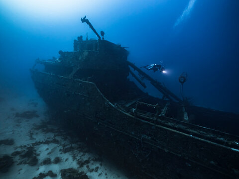 """Diver at Ship wreck """"Superior Producer"""" in turquoise water of coral reef in Caribbean Sea, Curacao"""