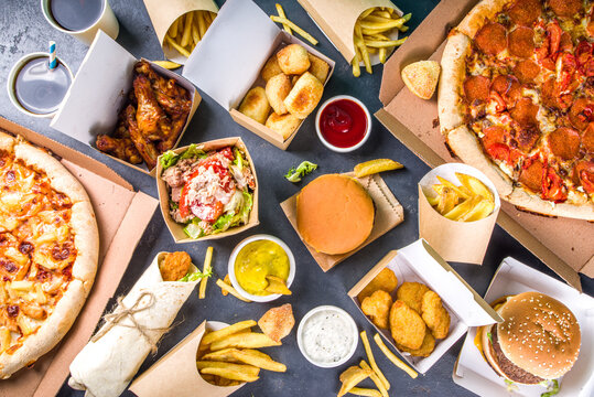 Delivery fastfood ordering food online concept. Large set of assorted take out foods pizza, french fries, fried chicken nuggets, burgers, salads, chicken wings, sides, black concrete background