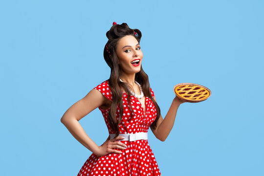 Happy pin up woman in polka dot red dress holding homemade sweet pie on blue studio background