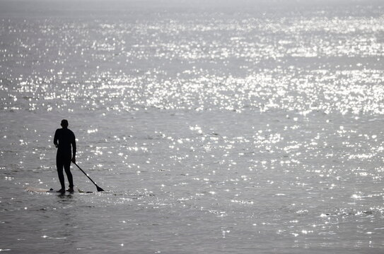 Man paddle boards during a sunny and warm weather near the beach in Saint-Brevin-Les-Pins