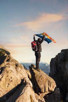 mountaineer summiting on a mountain rock and waving a rainbow flag of peace. hiking and mountain activities. trekking.