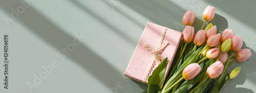 Bouquet of pink tulips and gift box isolated on green background with shadow. Spring flowers. Greeting card for Birthday, Woman, Mother's Day, Wedding, Valentine's day. Flat lay. Copy space. Banner