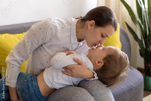 caucasian family little preschool baby boy and mom young woman hug joyfully together in living room at home with happiness smile. Child son congratulates on Mother's Day. Motherhood, childhood concept