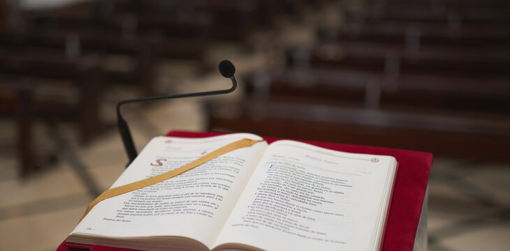 marble lectern with a red felt and a bible with some pews in the