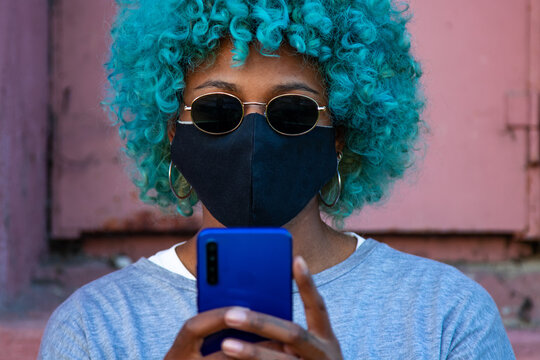 portrait of black afro american woman with mobile phone and mask