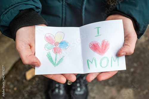 diy. girl holding in hands. cute postcard present for mother's day, March 8th. heart and flower, pretty drawing for mom.
