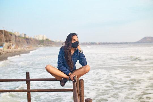 mujer joven con mascarilla feliz en la playa. Momento de relajacion a orillas del mar durante un atardecer. Fondo de olas y mar