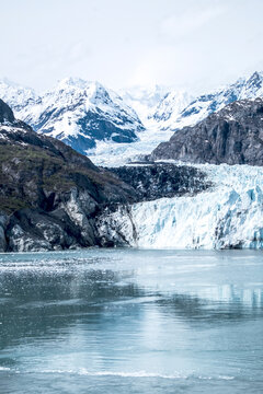 A glacier, a river of ice, winds down to the sea through steep mountainous terrain