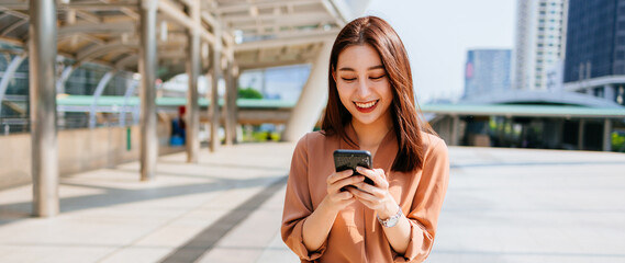 Fototapeta Beautiful young Asian woman in formal clothing standing outside office building using smartphone while browsing internet during break
