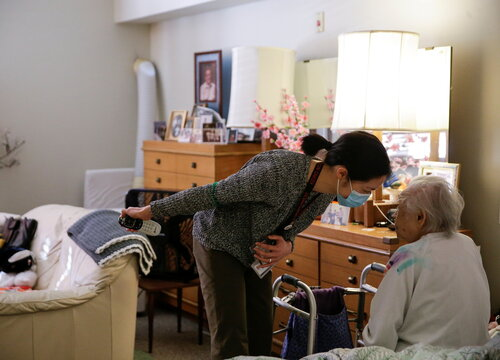 Iijima-Schergen tells Uomoto, 98, to close her eyes as her son and niece arrive for a surprise visit at Nikkei Manor, an assisted living facility in Seattle