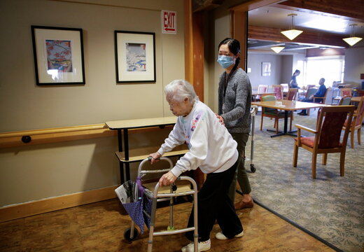 Uomoto, 98, is guided back to her room by Iijima-Schergen for a surprise visit from family at Nikkei Manor, an assisted living facility in Seattle