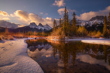 Three Sisters from Policeman Creek after sunrise reflected in the Bow River, Canmore, Alberta, Canada