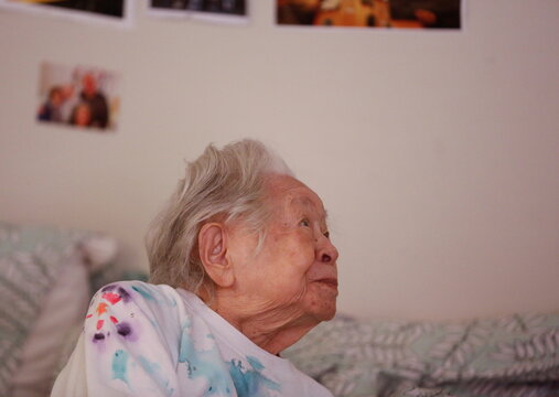 Uomoto, 98, looks at family members surprising her with a visit to her room at Nikkei Manor, an assisted living facility in Seattle