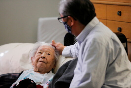Uomoto, 98, looks up at her son Uomoto as they visit in person for the first time in a year at Nikkei Manor, an assisted living facility in Seattle