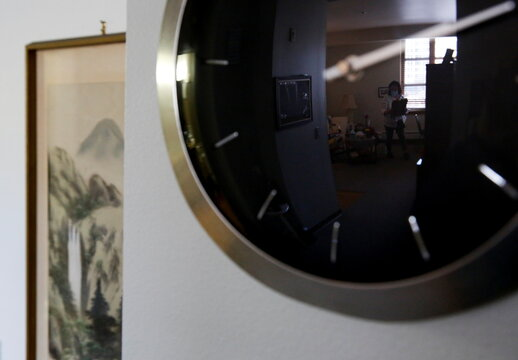 Reflected in a clock, Sakaguchi visits her mother Sakaguchi, 94, at Nikkei Manor, an assisted living facility in Seattle